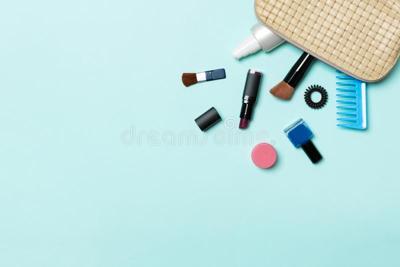Top view of make up products fallen out of cosmetics bag on blue background. Cosmetic concept with space for your design.  stock photos