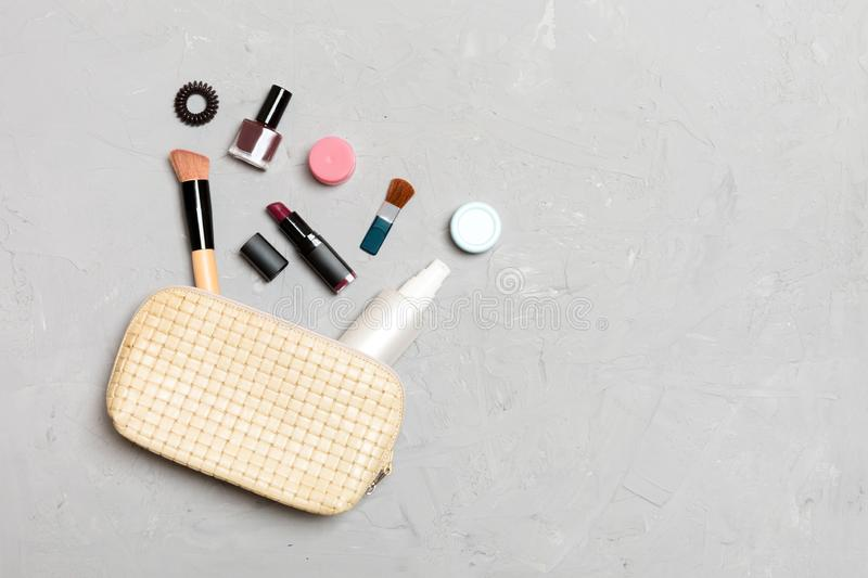 Top view of make up products fallen out of cosmetics bag on cement background. Cosmetic concept with space for your design.  stock image