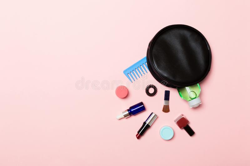Top view of make up products fallen out of cosmetics bag on pink background. Cosmetic concept with space for your design.  royalty free stock image