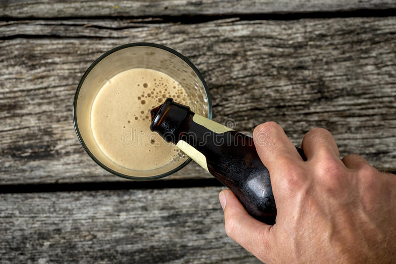 Top view of male hand pouring dark beer in a glass. Placed on textured rustic wooden boards royalty free stock photos