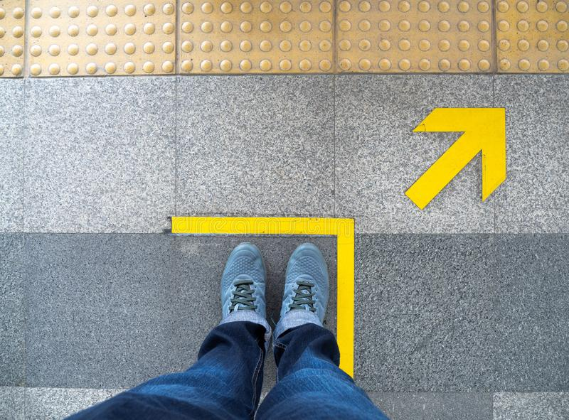 Top view of man feet standing over Arrow symbol on subway platform. Yellow arrow sign on floor at the train station.  royalty free stock photo