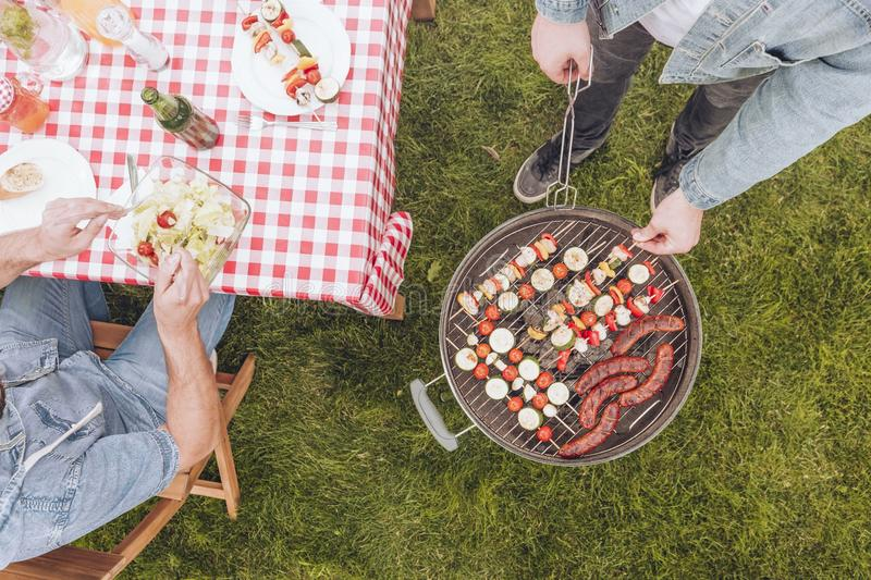 Top view on man next to grill with shashliks and sausages during outdoor party. Top view on men next to grill with shashliks and sausages during outdoor party royalty free stock photography