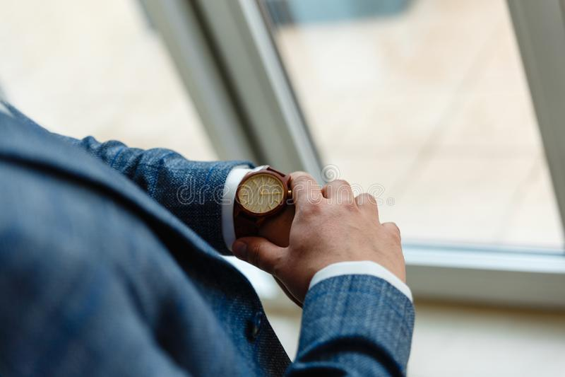 Top view of a man's hands in a suit looking at a wrist watch. Businessman is checking time on his modern wrist watch. Top view. S stock photo