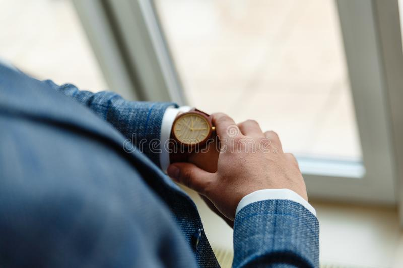 Top view of a man's hands in a suit looking at a wrist watch. Businessman is checking time on his modern wrist watch. Top view. S royalty free stock photography
