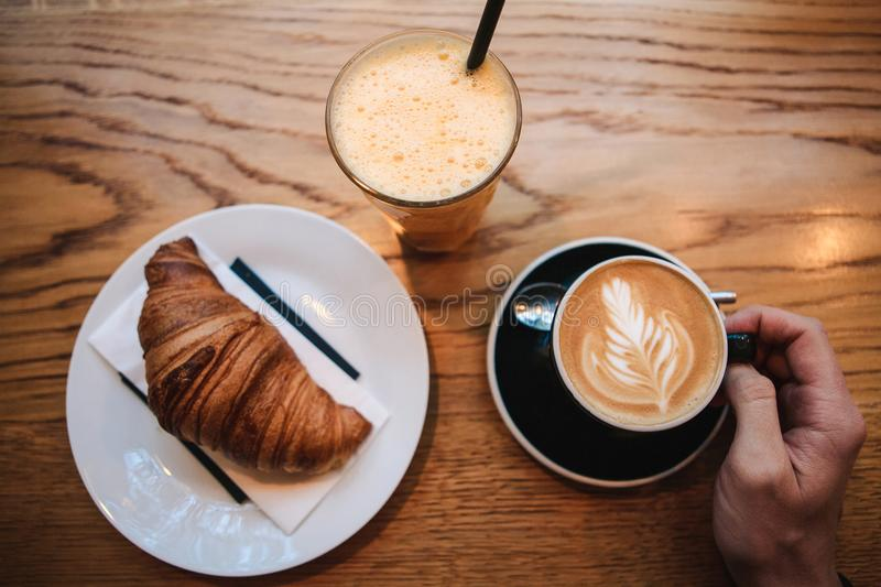 Top view. A man takes a cup of hot fragrant cappuccino. Near the table is a croissant and a glass with fresh orange royalty free stock photography