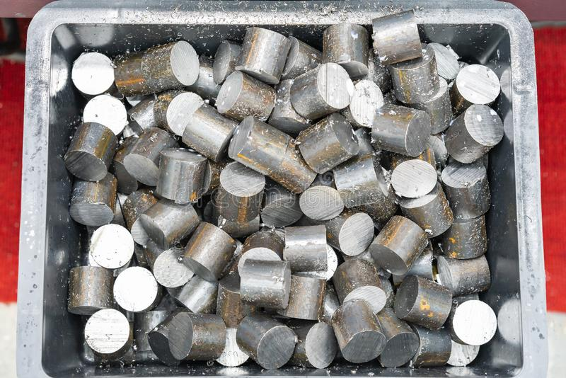 Top view many round shaft steel piece after cutting by automatic continuous and high speed band saw or circular saw machine in box stock photos