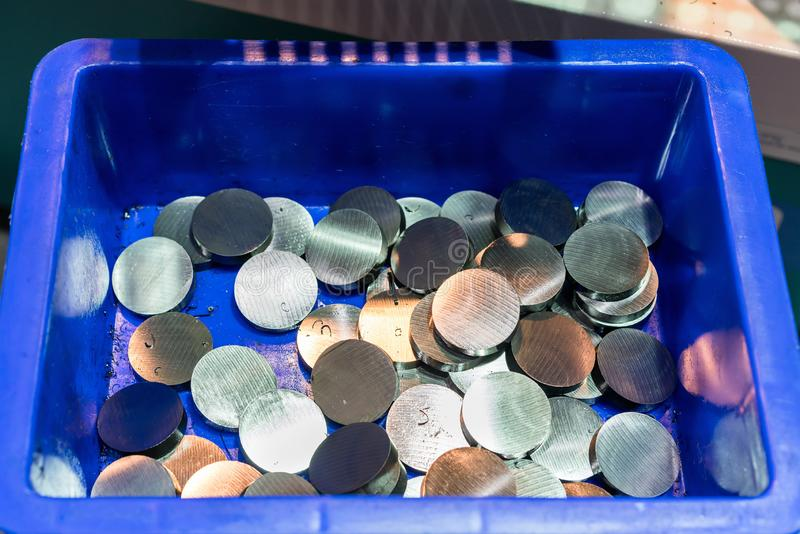 Top view many steel piece round shape after cutting by band saw machine in blue plastic box.  stock images