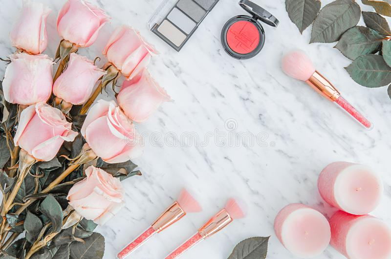 Top view marble background with beautiful roses. pink candles and cosmetics. Flat lay royalty free stock image