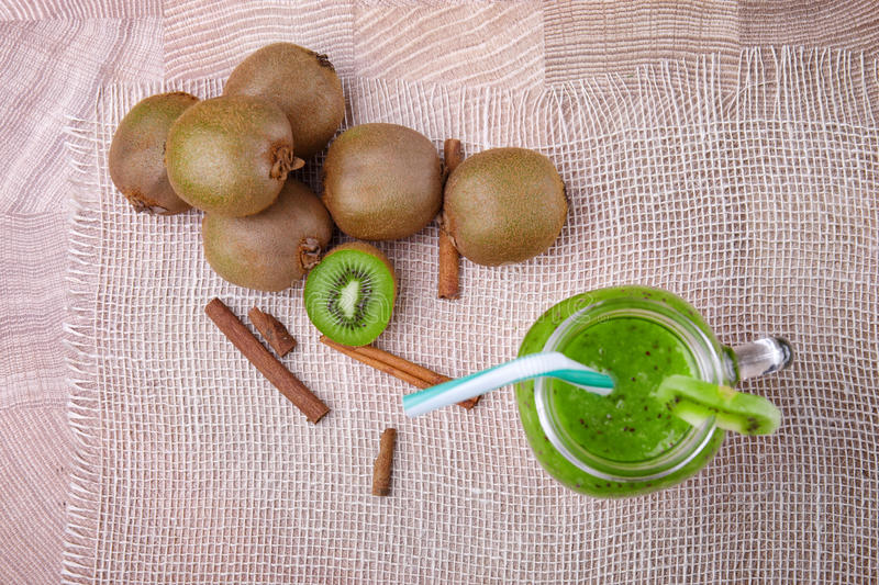 Top view of a mason jar full of kiwi smoozie with drinking straw and a slice of kiwi on a light wooden background. A stock image