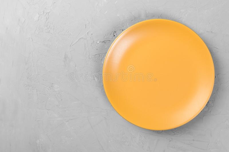 Top view of matte round empty orange plate on dark cement background space for you design royalty free stock photos