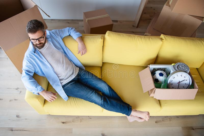 Top view of mature man with boxes moving in new house, relaxing on sofa. royalty free stock photography
