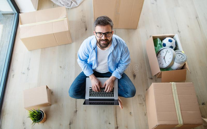 Top view of mature man with boxes moving in new house, using laptop. stock photography