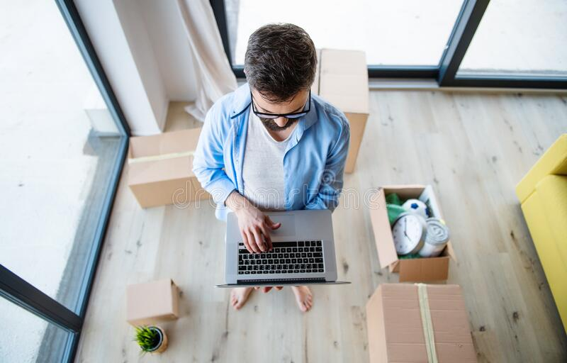 Top view of mature man with boxes moving in new house, using laptop. royalty free stock image
