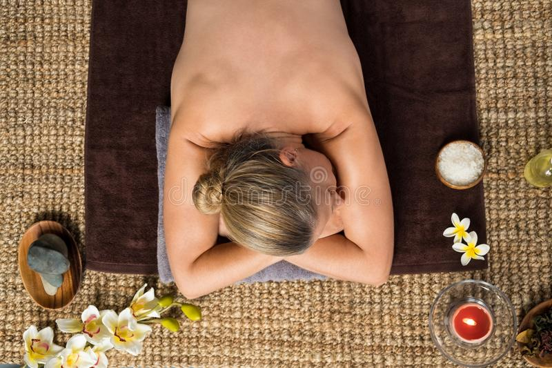 Mature woman relaxing at spa center stock image
