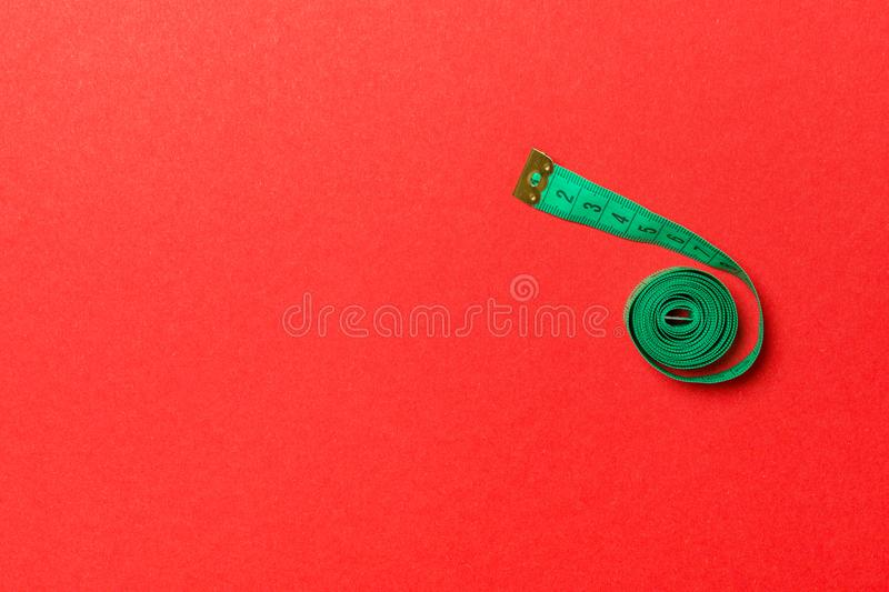 Top view of measure tape curtailed into a spiral with copy space. Concept of sewing accessory or healthy diet on red background royalty free stock images