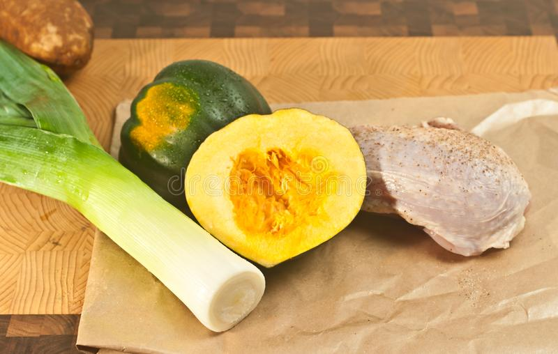 Salted and peppered raw, organic, chicken breast, washed leek, and potato, and split acorn squash, on a bamboo wood cutting board,. Top view,medium distance, of royalty free stock photography