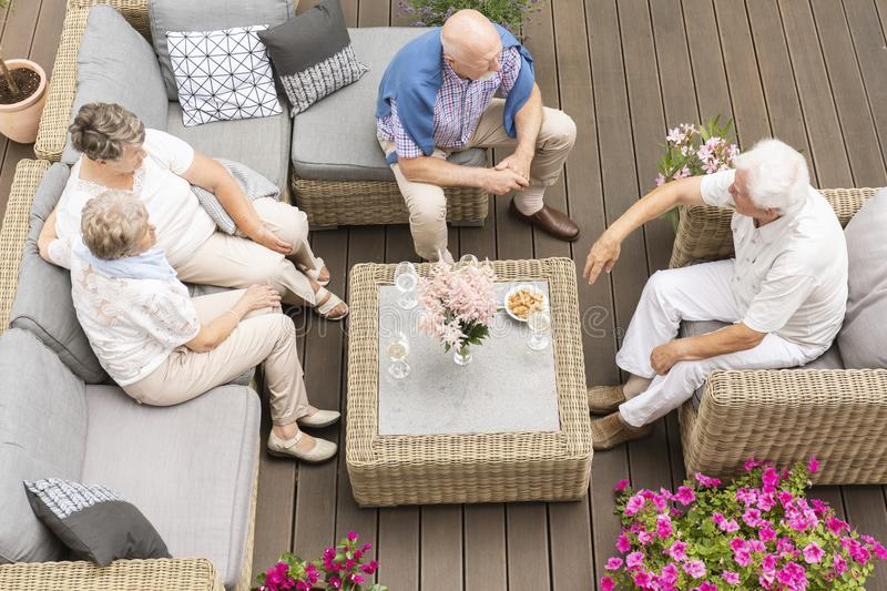Top view on meeting of active elderly people on terrace with flo stock image