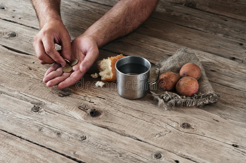 Top view of a men hands that they consider cents on the wooden background closeup. Next to the table is a cup of water, a piece of bread and potatoes. Copy royalty free stock images