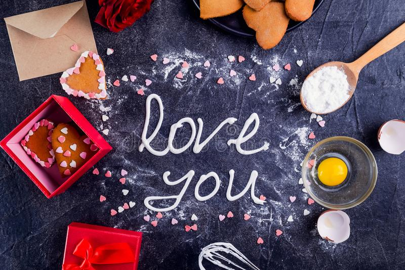 Top view meringue cream lettering Love you on the black stone background with ingredients, flower, gift box with cookies and decor. Details. Valentine`s day royalty free stock photography