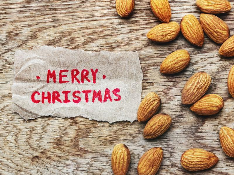 Top view of the Merry christmas inscription in red pencil on piece of wrapping paper, on a wooden board and scattered almonds. Top view of the Merry christmas stock photo