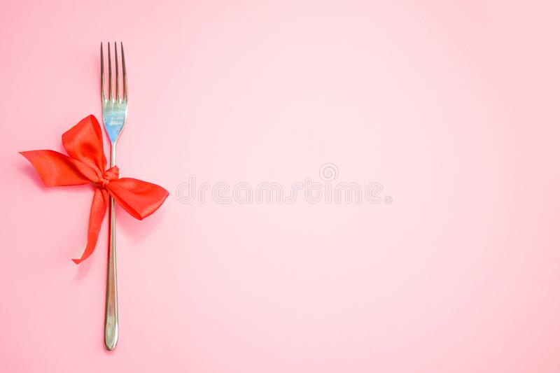 Top view of metal fork with red bow on pink background. space for text. Christmas, New Year, Birthday food, holidays, celebration royalty free stock image
