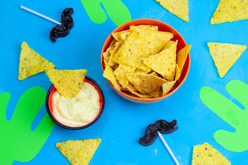 mexican party table food and decorations corn chips nachos with sauce,paper cut cactuses and caramel moustaches on blue royalty free stock photography