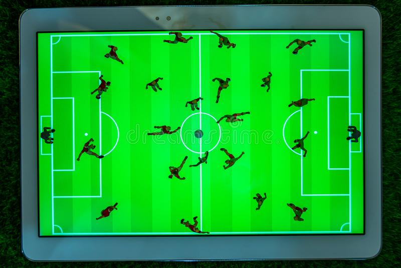 Top view of miniature toys figurines football soccer players on a computer pad royalty free stock images