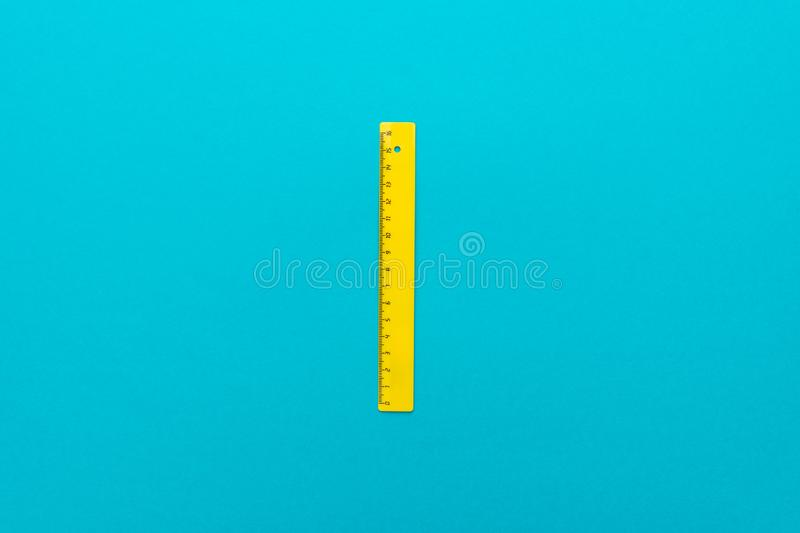 Top view minimalist photo of yellow plastic ruler with central composition. Minimalist flat lay photo of yellow plastic ruler on the turquoise blue background royalty free stock images