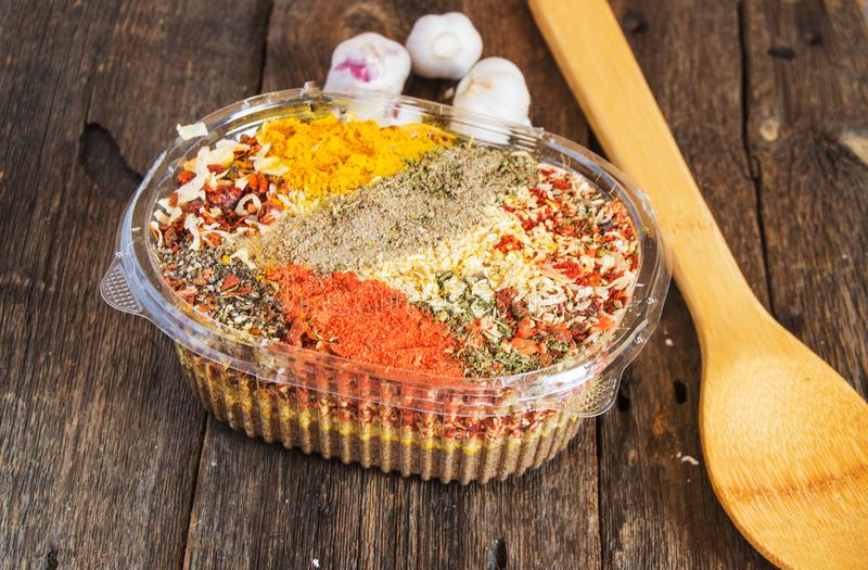 Top view of mixed dry Indian colorful spices in a plastic container next to a wooden spoon on a dark wooden background. Concept of Asian cuisine with culinary stock photo