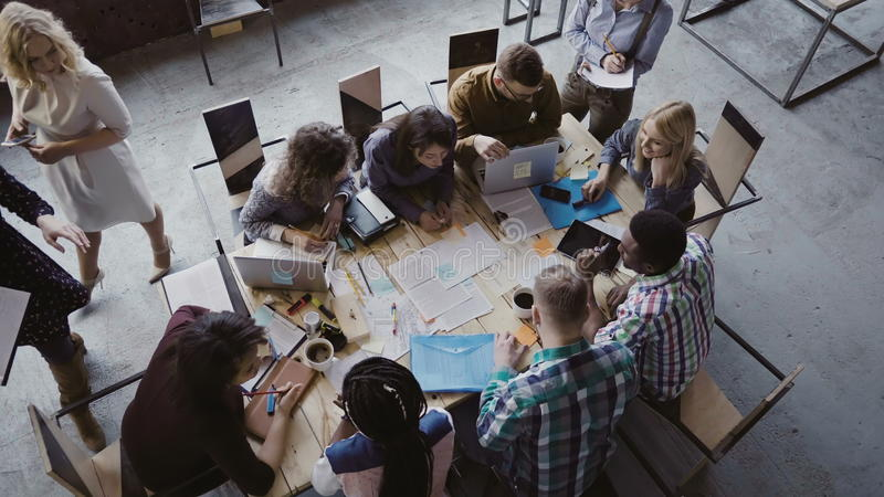Top view of mixed race business team sitting at the table at loft office and working. Woman manager brings the document. royalty free stock photos