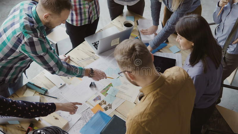Top view of mixed race group of people standing near the table. Young business team working on start-up project together royalty free stock image