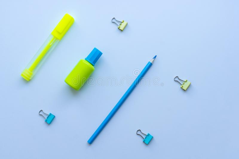 Top view of mixed stationery in yellow and blue colours: clips, correction fluid, pencil and marker pen on white background. Conce stock photos