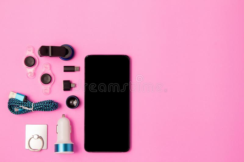 top view mobile device with mobile blank space for text,.accessories. micro USB Adapter, macro lens on pink background royalty free stock photos