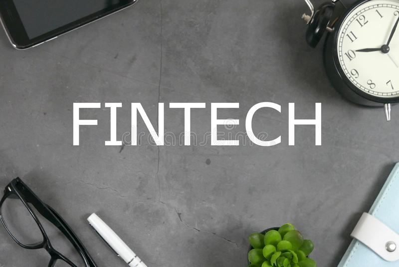 Top view of mobile phone, clock,notebook,plant,pen, and sunglasses on grey floor written with FINTECH. Financial Technology stock photos