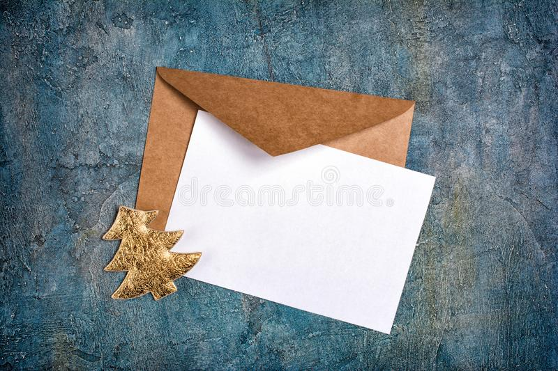Top view of mock-up blank white greeting christmas card with brown envelope and golden tree stock photo
