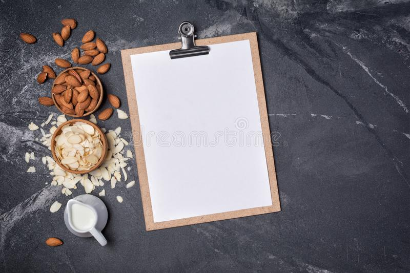 Top view of mock-up composition with clipboard and blank white sheet of paper with ingredients for almond milk. Top view of mockup composition with clipboard and royalty free stock image