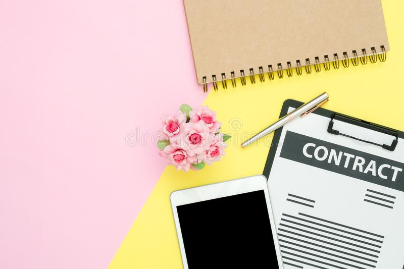 Top view mock up of contract, pen and black screen tablet, notebook with roses on pink yellow pastel color with copy space. Flat lay design office desk working royalty free stock photography