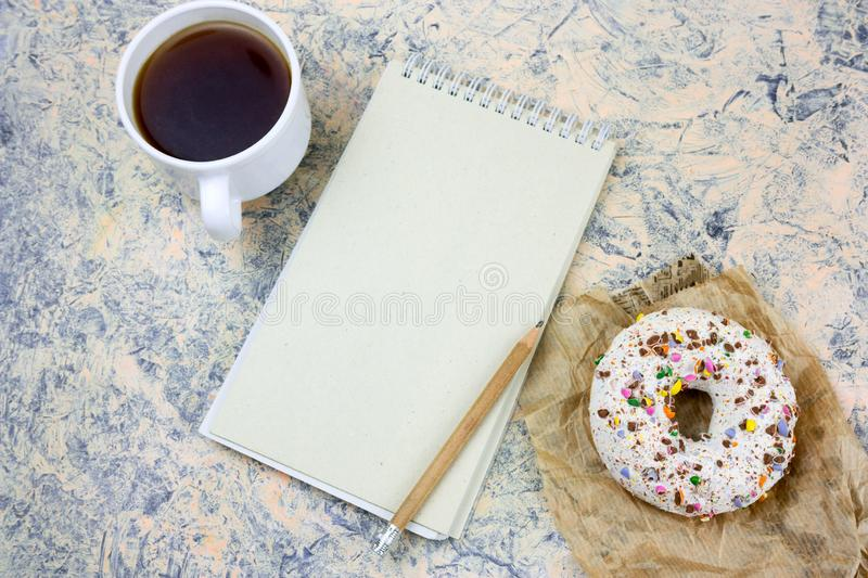 notebook with blank white paper sheet ,coffee cup and donut stock photos