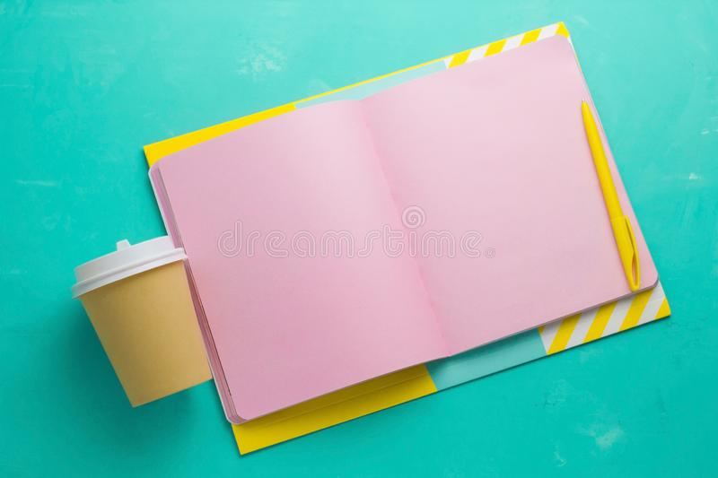 mock up open notepad with blank pink paper sheetscoffee to go cup a vibrant blue background stock image