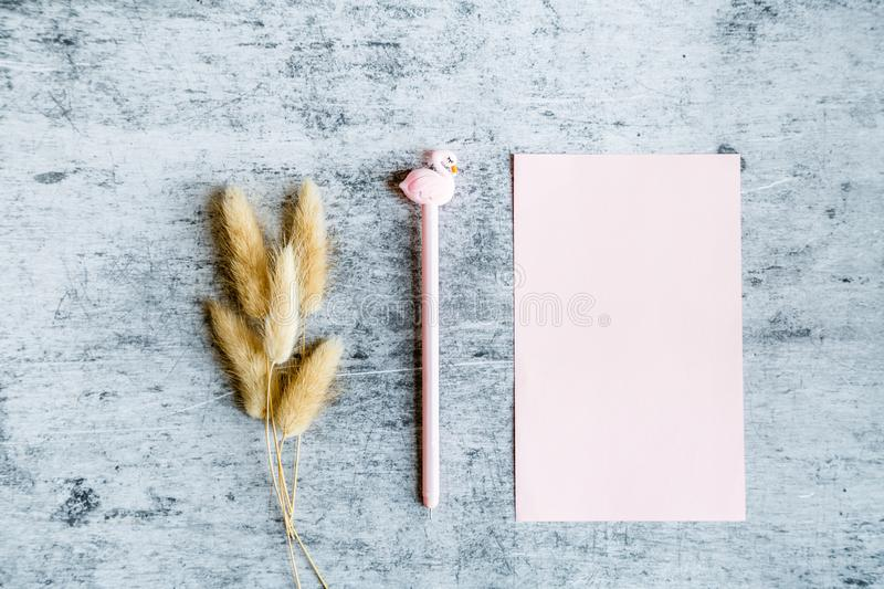 Top view mockup of blank pink paper, dry flowers and pen with flamingo on gray concrete background. Flat lay, copy space, business royalty free stock images