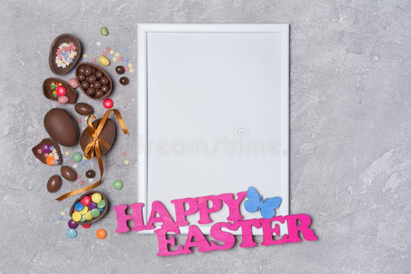 Mock up of blank white frame with pink text of happy easter and traditional sweets as chocolate eggs and bright colorful sugar royalty free stock images