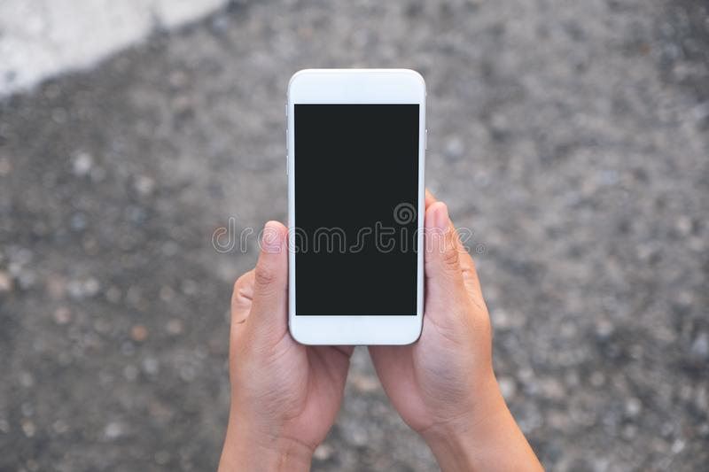 Mockup image of hand holding white mobile phone with blank black screen with street background. Top view mockup image of hand holding white mobile phone with stock photos