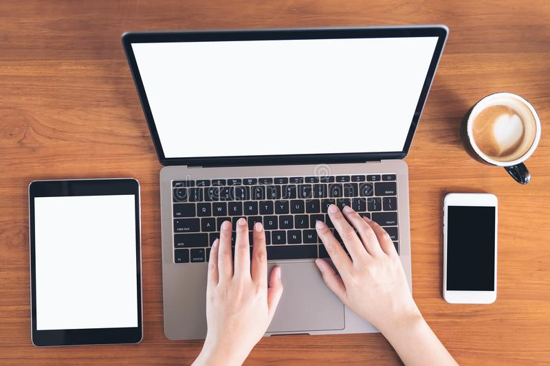 Top view mockup image of hands using and typing on laptop with blank white screen , tablet pc , mobile phone and coffee cup. On wooden table stock photos