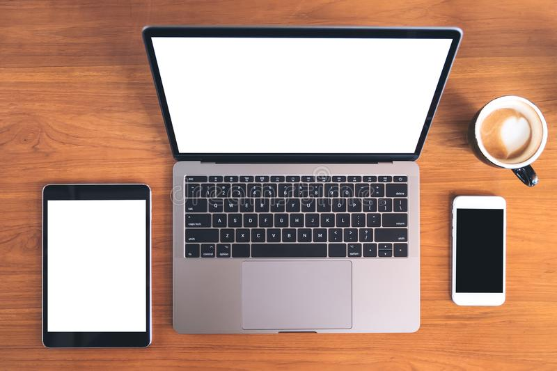Top view mockup image of laptop with blank white screen , tablet pc , mobile phone and coffee cup. On wooden table stock photo