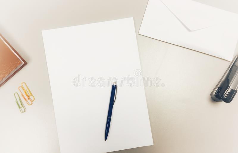 Top view of modern desk office workplace with notepad, envelope, a4 paper, pen, paper clips and stapler royalty free stock photos