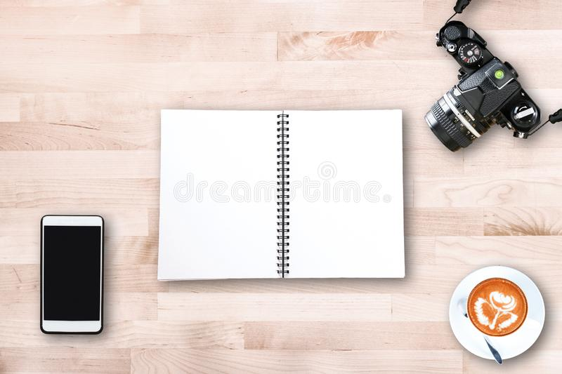 Top view of modern office workplace with vintage film camera , smart phone , notebook paper , latte art coffee cup on wooden table royalty free stock image