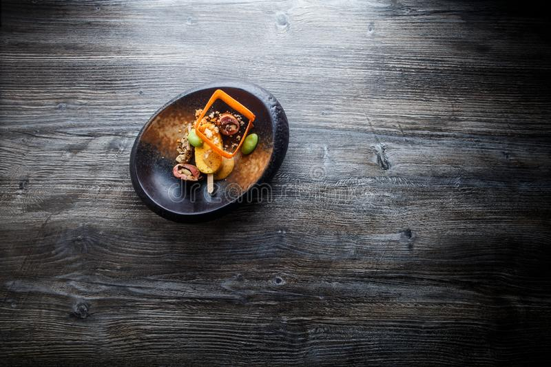 Top view modern restaurant fish dish with beautiful garnish. Decoration served in original black plate on wooden table royalty free stock photos