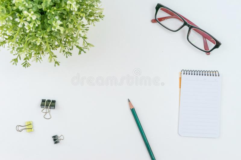 Top View of Modern working Place on White Office Desk with green Flower Notepad Pen Glasses and Convenient clip office supplies royalty free stock image