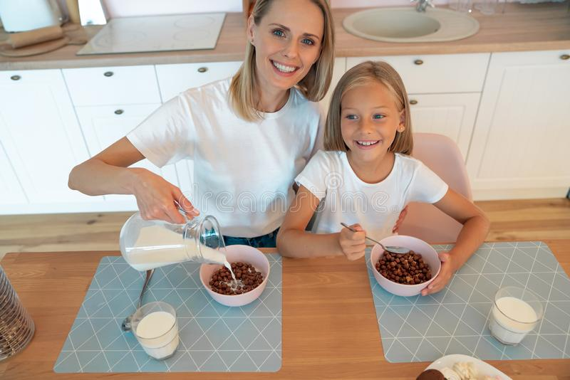 Top view of a mom pouring milk to her daughter for breakfast with chocolate flakes. have a good time together, dressed alike.  royalty free stock images