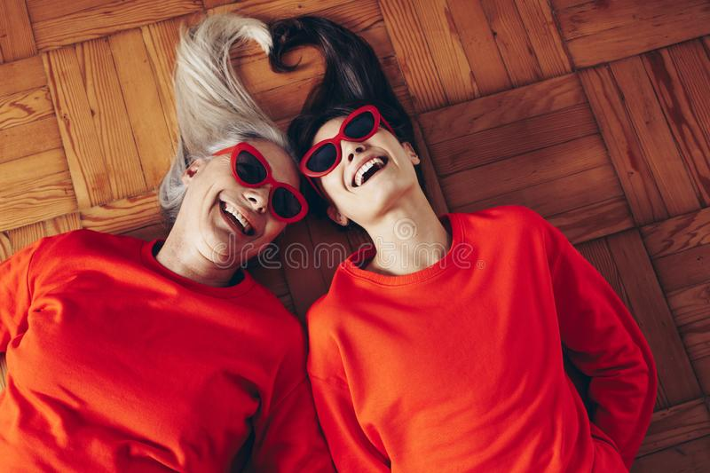 Top view of mother and daughter lying on floor with heads togeth royalty free stock image